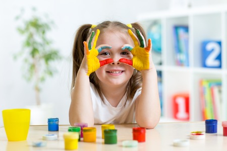 Photo pour cute cheerful kid girl showing her hands painted in bright colors - image libre de droit