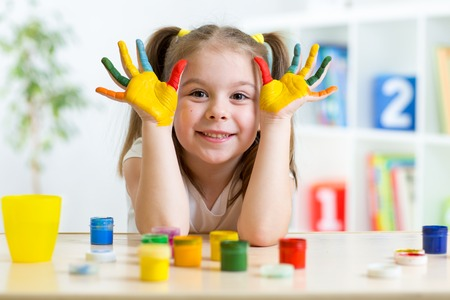 Photo pour Portrait of kid girl with face and hands painted at home - image libre de droit