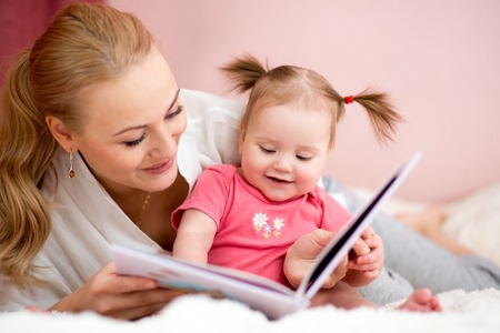 happy mother read a book to baby girl at home