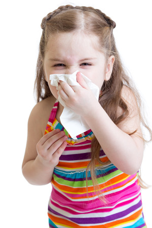 sick child wiping or cleaning nose with tissue isolated on white