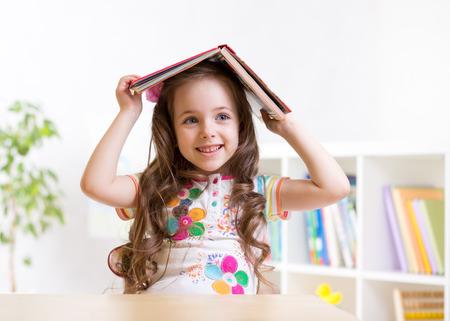preschooler  kid girl with book over her head indoors