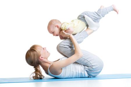 Foto de mother and baby make gymnastics, yoga exercises isolated on white - Imagen libre de derechos
