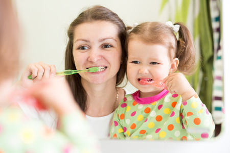 Photo for mother teaching kid teeth brushing in bathroom - Royalty Free Image