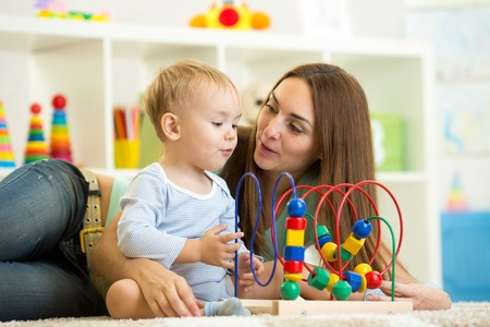 child boy and mother playing with educational toy
