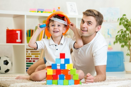 Foto de kid boy and father play builders in children room - Imagen libre de derechos