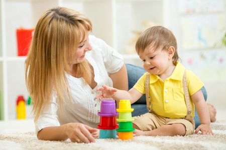 mom and child toddler play toys in nursery at home