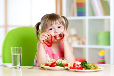 Foto de child eating healthy food in kindergarten or at home - Imagen libre de derechos