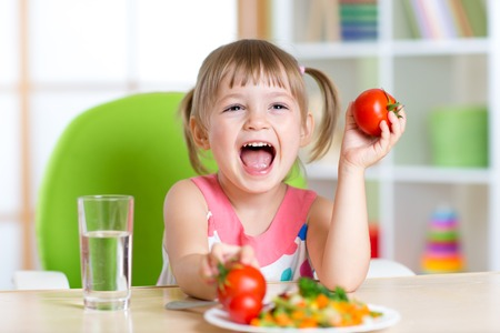 Foto de happy child girl eats dinner and shows tomatoes - Imagen libre de derechos