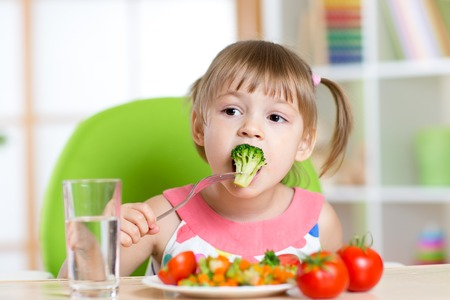 Foto de Child little girl eats vegetable salad using fork - Imagen libre de derechos