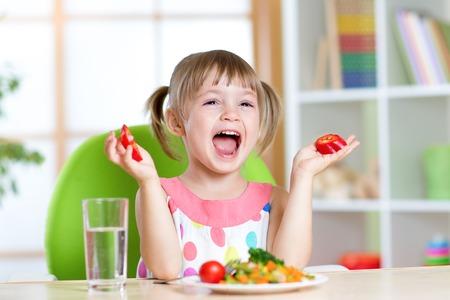 kid girl eating healthy vegetables food at home or kindergarten