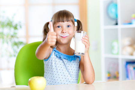 child girl drinks milk and showing thumb up