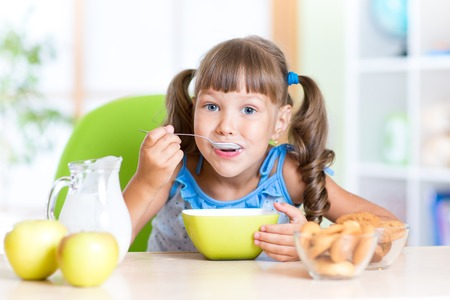 cute child girl eating cereal with milk in nursery