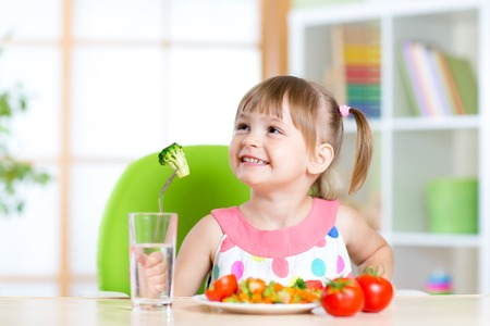 Foto de Kid eats healthy vegetables meal in home or nursery - Imagen libre de derechos