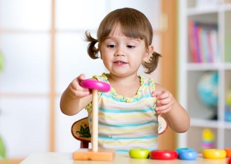 Foto de Child girl playing with toy indoors at home - Imagen libre de derechos