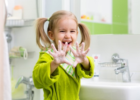 child washing hands and showing soapy palms