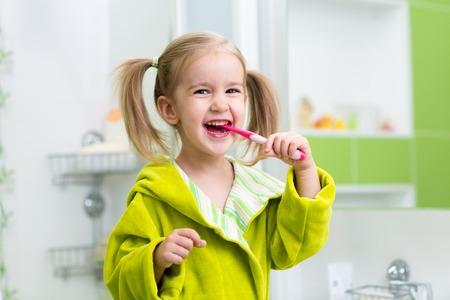 Smiling child kid girl brushing teeth in bathroom