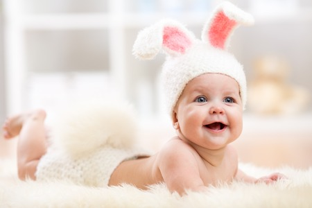 Smiling cute baby child in rabbit costume lying on fur in nursery