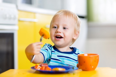 Cute child little boy eating healthy food in kitchen
