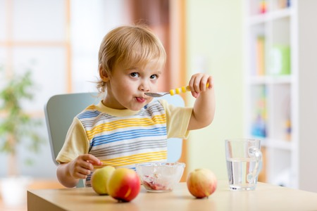 Cute child eating healthy food with a spoon at home