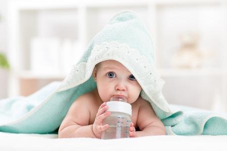 Foto de Adorable child baby drinking water from bottle. Little girl  wrapped bathing towel lying on bed. - Imagen libre de derechos