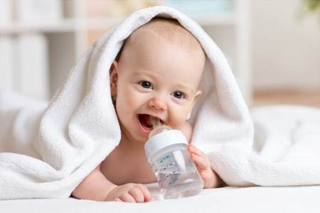 Happy baby boy drinks water from bottle wrapped towel after bath
