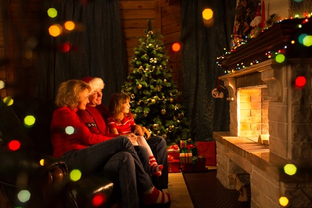 Happy family - mother, father and their daughter by a fireplace on Christmasの写真素材