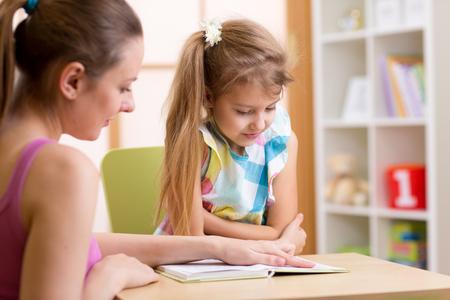 Foto de Child Pupil Reading With Teacher In Elementary School - Imagen libre de derechos