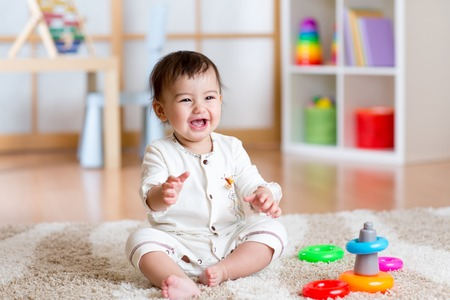 Foto de cute cheerful baby playing with colorful toy pyramid at home - Imagen libre de derechos