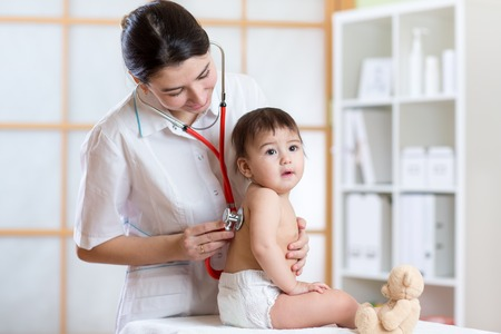 doctor woman examining lungs of little child with stethoscope