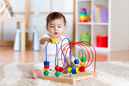 Foto de toddler girl playing with colorful toy in nursery room - Imagen libre de derechos