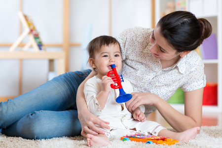 Photo pour baby and mom playing with musical toys - image libre de droit