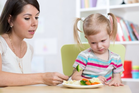 Child girl looks with disgust at healthy vegetables. Mom convinces daughter to eat food.