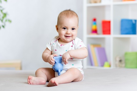 Photo pour cheerful baby playing with toy at home - image libre de droit