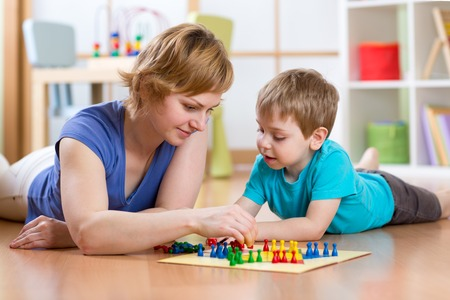 Photo pour Family mother and son kid playing board game ludo at home on the floor - image libre de droit
