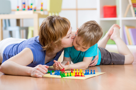 Photo pour Family mother and son kid playing board game ludo and kissing at home on the floor - image libre de droit