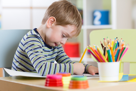 Preschool child boy use pencils and paints for homework received from kindergarten
