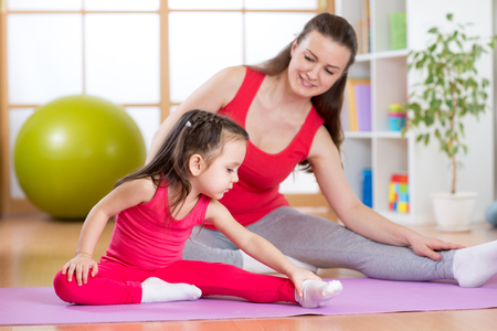 Foto de Mother and child daughter doing yoga exercises on mat at home - Imagen libre de derechos