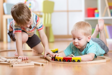 Cute children playing with wooden train. Toddler kids playing with blocks and trains. Boys building toy railroad at home or daycare. Educational toys for preschool and kindergarten child.