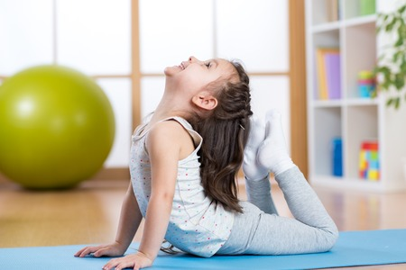 Photo for Child girl doing gymnastics on mat at home - Royalty Free Image