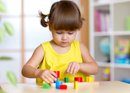 Photo pour Little girl child kid playing with sorter toys in nursery - image libre de droit