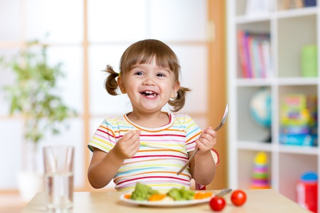 Photo pour Happy kid girl eating vegetables. Healthy nutrition for children - image libre de droit