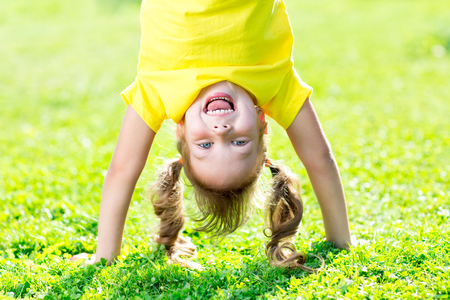 Photo pour Portraits of happy kid playing upside down outdoors in summertime standing on hands - image libre de droit