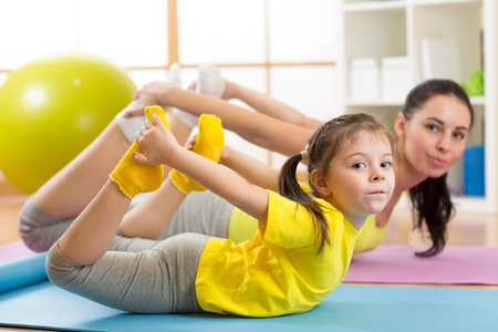 Mother and child doing yoga exercises on rug at home.
