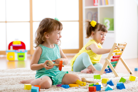 Foto de Little kids girls playing with abacus and constructor toys in kindergarten, playschool or daycare center - Imagen libre de derechos