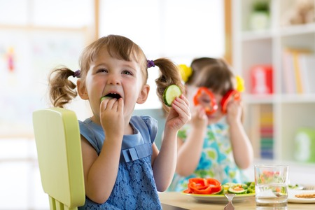 Foto de children kids eating vegetables in kindergarten or at home - Imagen libre de derechos