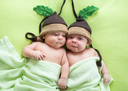 Foto de Twins brothers babies weared in acorn hats - Imagen libre de derechos