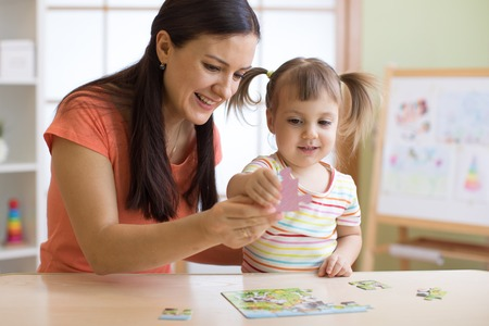 Foto de mother and daughter doing playing puzzle toy together on the table in children room - Imagen libre de derechos