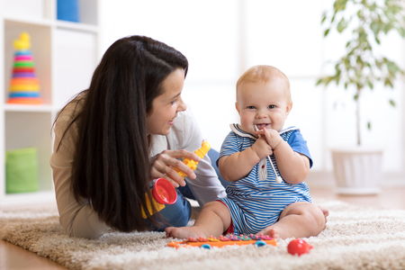 Photo pour mom and baby playing musical toys at home - image libre de droit