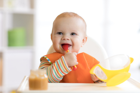 Photo pour Happy infant baby boy spoon eats itself - image libre de droit