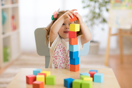 Foto de Kid girl playing with block toys in day care center - Imagen libre de derechos